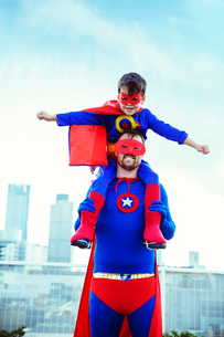 Superhero father carrying son on shoulders on city rooftopの写真素材 [FYI02188992]