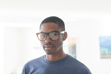 Portrait of young businessman wearing glasses standing in officeの写真素材 [FYI02188999]
