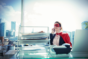 Businesswoman in cape and mask talking on phone at office deskの写真素材 [FYI02189002]