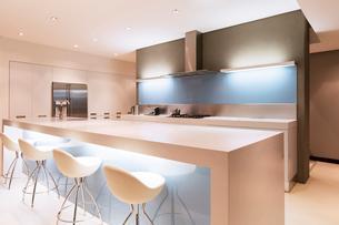 Modern white kitchen with kitchen island and stools illuminated at nightの写真素材 [FYI02189007]