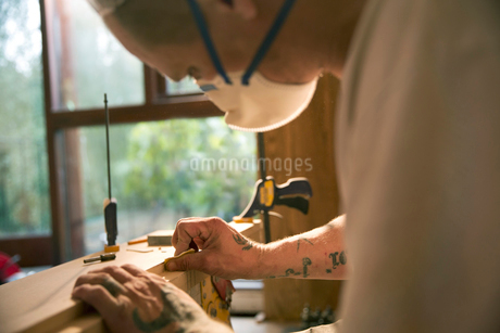 Close up construction worker with tattoos examining wood boardの写真素材 [FYI02189010]
