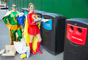 Superhero couple recycling on city sidewalkの写真素材 [FYI02189039]