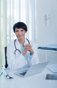 Portrait of smiling female doctor sitting at desk with laptop in officeの写真素材 [FYI02189056]