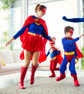 Family of superheroes playing in living roomの写真素材 [FYI02189105]
