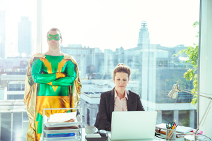 Superhero standing near businesswoman working in officeの写真素材 [FYI02189127]