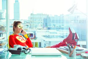 Superhero talking on cell phone at office deskの写真素材 [FYI02189140]