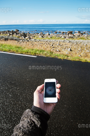 Lofoten, Norge, Hand holding smartphone with compassの写真素材 [FYI02189191]