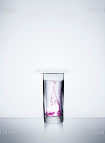 Purple liquid in glass of waterの写真素材 [FYI02189197]