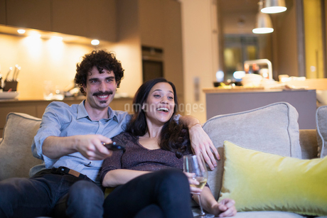 Happy couple watching TV and drinking white wine on living room sofaの写真素材 [FYI02189219]