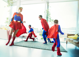Superhero family chasing each other in living roomの写真素材 [FYI02189230]