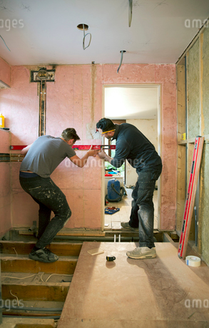 Construction workers using level tool in houseの写真素材 [FYI02189281]