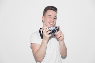 Portrait smiling, confident teenage boy with retro cameraの写真素材 [FYI02189325]