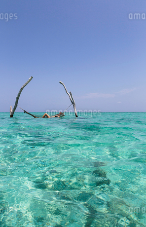 Young woman laying in hammock over tranquil blue ocean, Maldives, Indian Oceanの写真素材 [FYI02189339]