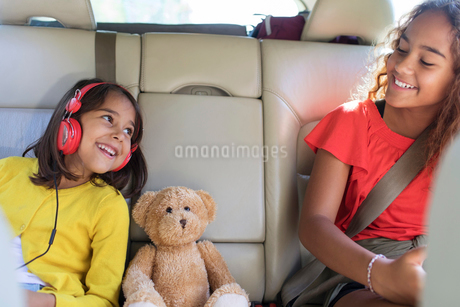 Happy sisters and teddy bear riding in back seat of carの写真素材 [FYI02189344]