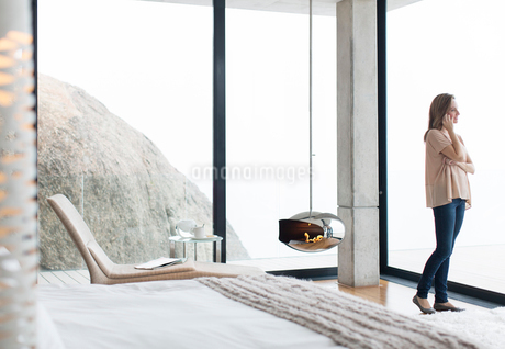 Woman talking on cell phone in modern bedroomの写真素材 [FYI02189375]