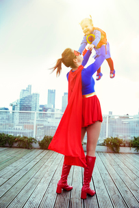 Superhero mother playing with daughter on city rooftopの写真素材 [FYI02189406]