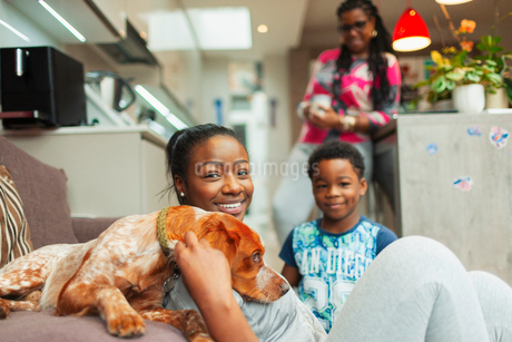Portrait smiling family with dog at homeの写真素材 [FYI02189428]