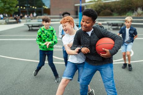Tween boys playing basketball in schoolyardの写真素材 [FYI02189455]
