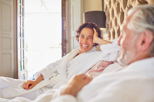 Happy, laughing mature couple relaxing on hotel bedの写真素材 [FYI02189481]