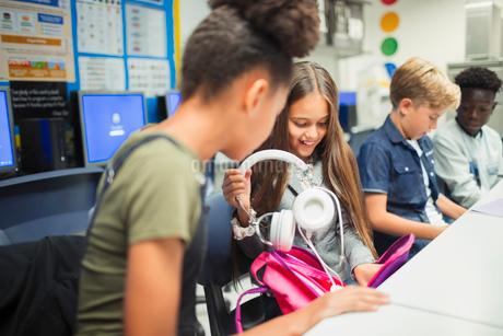Junior high school girl student removing headphones from backpack in classroomの写真素材 [FYI02189510]
