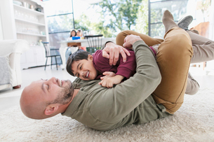 Playful father and son hugging on floorの写真素材 [FYI02189539]