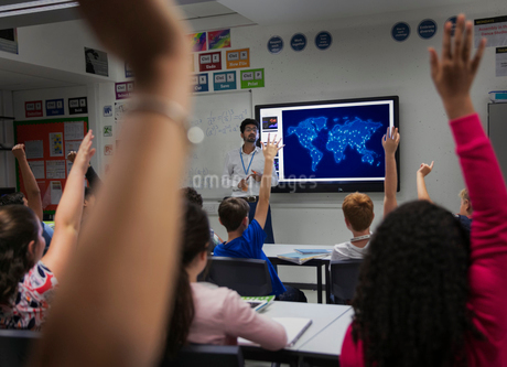Junior high school students participating with hands raised in classroomの写真素材 [FYI02189551]