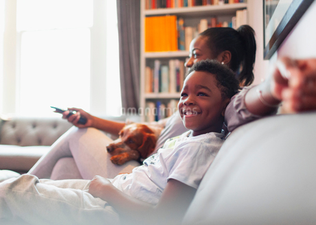 Happy boy watching TV with mother and dog on living room sofaの写真素材 [FYI02189574]