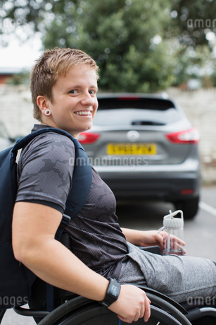 Portrait confident young female university student in wheelchair in parking lotの写真素材 [FYI02189610]