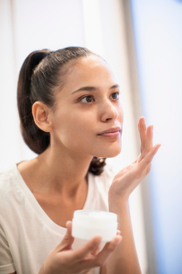Woman applying moisturizer to face in mirrorの写真素材 [FYI02189639]