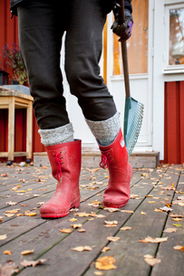 Nacka, Uppland, Sweden, Woman wearing rubber boots holding rの写真素材 [FYI02189669]