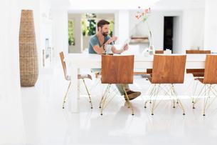 Man using digital tablet at breakfast table in modern dining roomの写真素材 [FYI02189784]