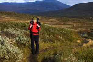 Sweden, Jamtland, Woman hiking among hillsの写真素材 [FYI02189785]