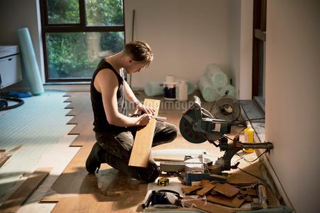 Construction worker preparing hardwood flooring in houseの写真素材 [FYI02189820]