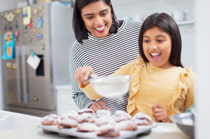 Mother and daughter baking muffins in kitchenの写真素材 [FYI02189822]