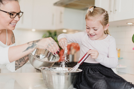 Mother and daughter baking in kitchenの写真素材 [FYI02189872]