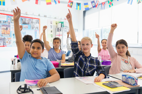 Eager junior high school students with hands raised in classroomの写真素材 [FYI02189878]