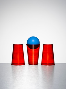 Blue ball in middle of three red cupsの写真素材 [FYI02189958]