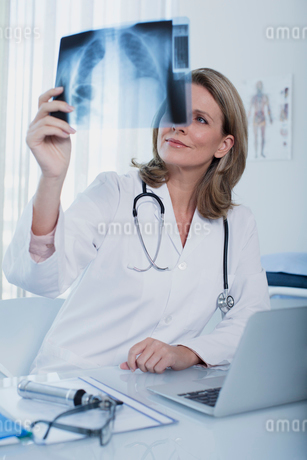 Female doctor looking at x-ray at desk with laptop in officeの写真素材 [FYI02189964]