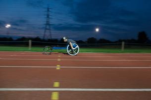 Young female paraplegic athlete speeding along sports track in wheelchair race at nightの写真素材 [FYI02190004]
