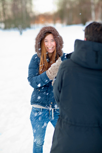 Sweden, Portrait of young woman playing with snow balls withの写真素材 [FYI02190076]