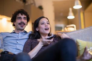 Couple watching TV on sofaの写真素材 [FYI02190095]