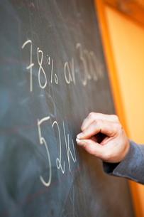 Sweden, Close-up of teacher writing on blackboardの写真素材 [FYI02190188]