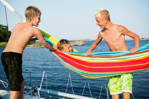 Sweden, Three teenage boys (14-15,16-17) on boat deck, on ofの写真素材 [FYI02190190]