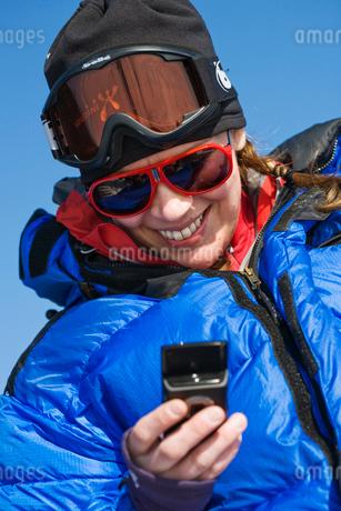 Sweden, Jamtland, Sylarna, Woman in ski clothing using mobilの写真素材 [FYI02190195]