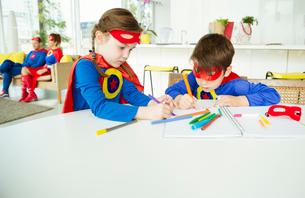 Superhero children drawing at tableの写真素材 [FYI02190244]