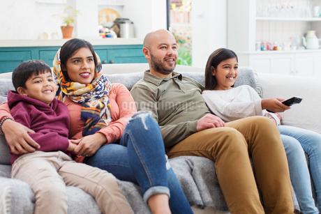 Family watching TV on living room sofaの写真素材 [FYI02190285]
