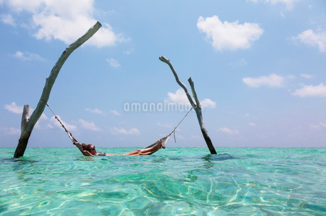 Woman laying in hammock over tranquil ocean, Maldives, Indian Oceanの写真素材 [FYI02190303]