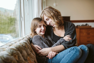 Affectionate mother and daughter cuddling on living room sofaの写真素材 [FYI02190327]