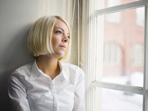 Sweden, Woman sitting on window sill and looking through winの写真素材 [FYI02190405]
