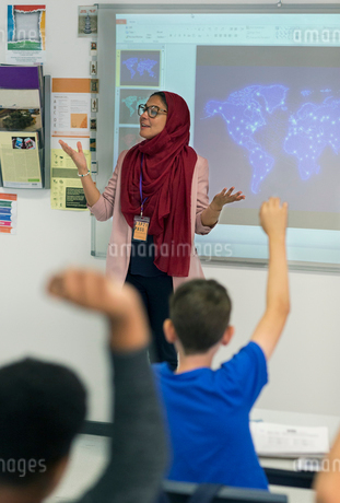 Female teacher in hijab leading lesson at projection screen in classroomの写真素材 [FYI02190500]